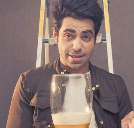 Aparshakti Khurana at a photoshoot holding a huge beer glass.