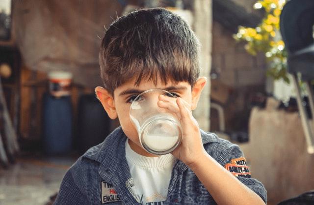 Child drinking milk in glass